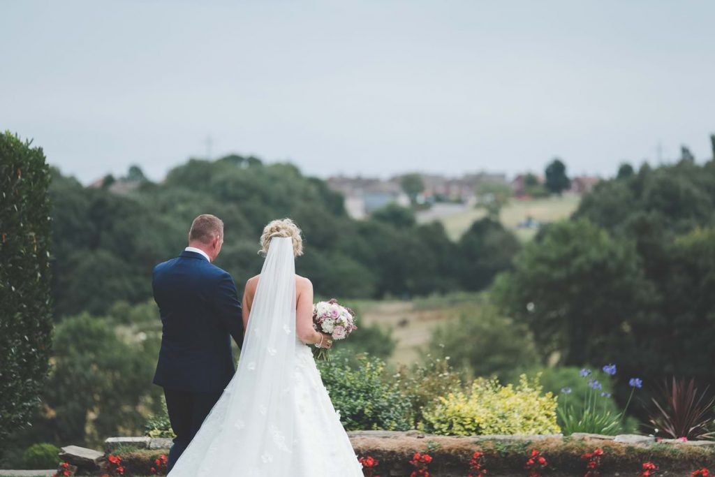 Choosing a wedding photographer. Couple looking out over the countryside at their Yorkshire wedding.
